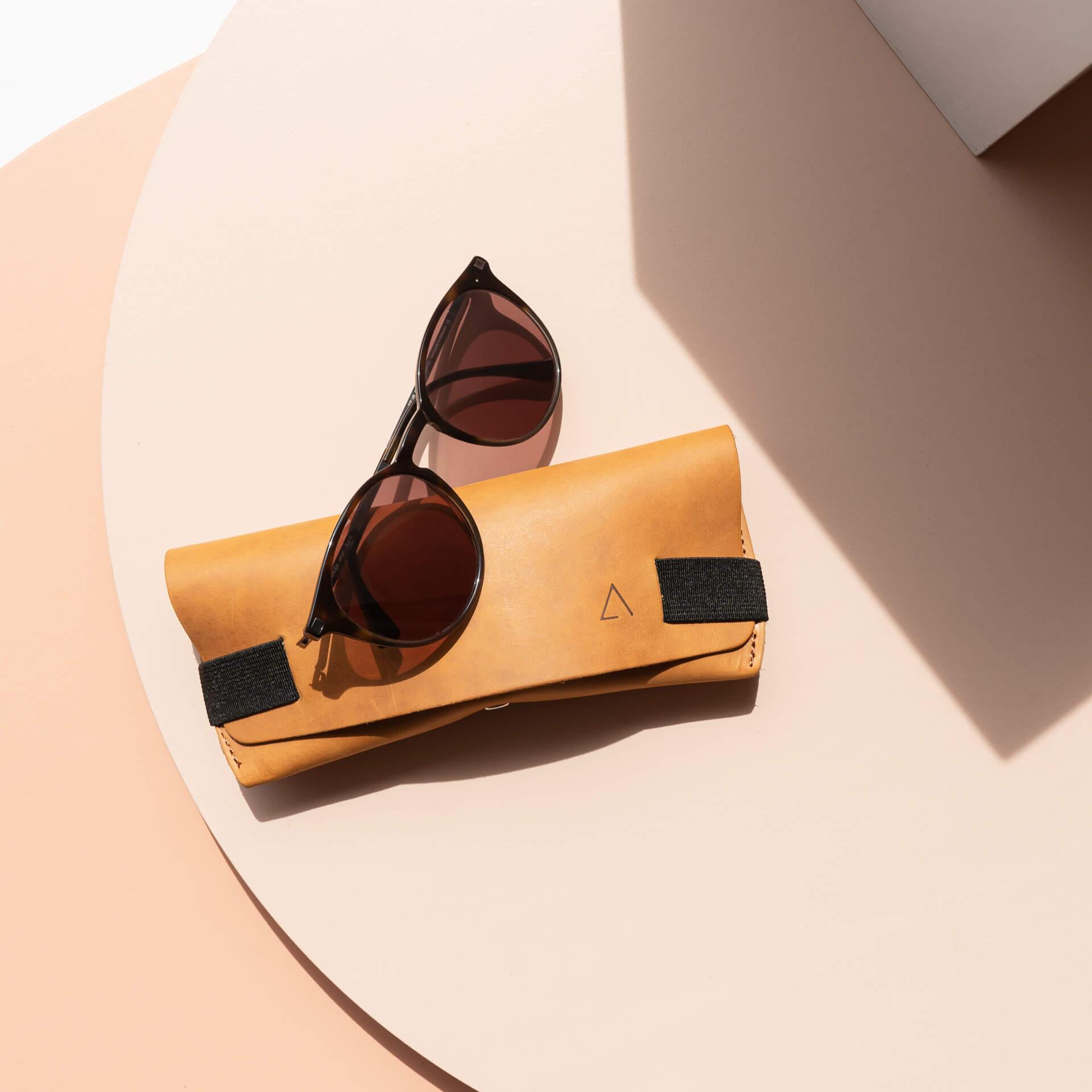 Brillenetui LUK aus nachhaltigem Naturleder in Cognac mit schwarzem Verschlussband von vorn mit Sonnenbrille