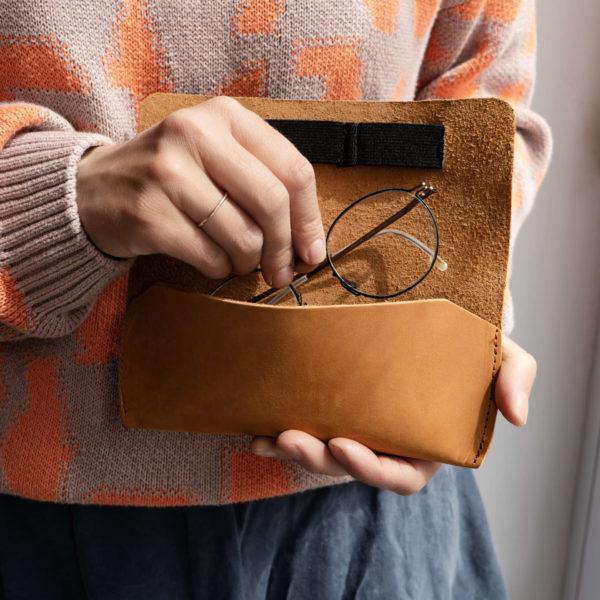 Frau legt Brille in Brillenetui LUK aus nachhaltigem Naturleder in Cognac