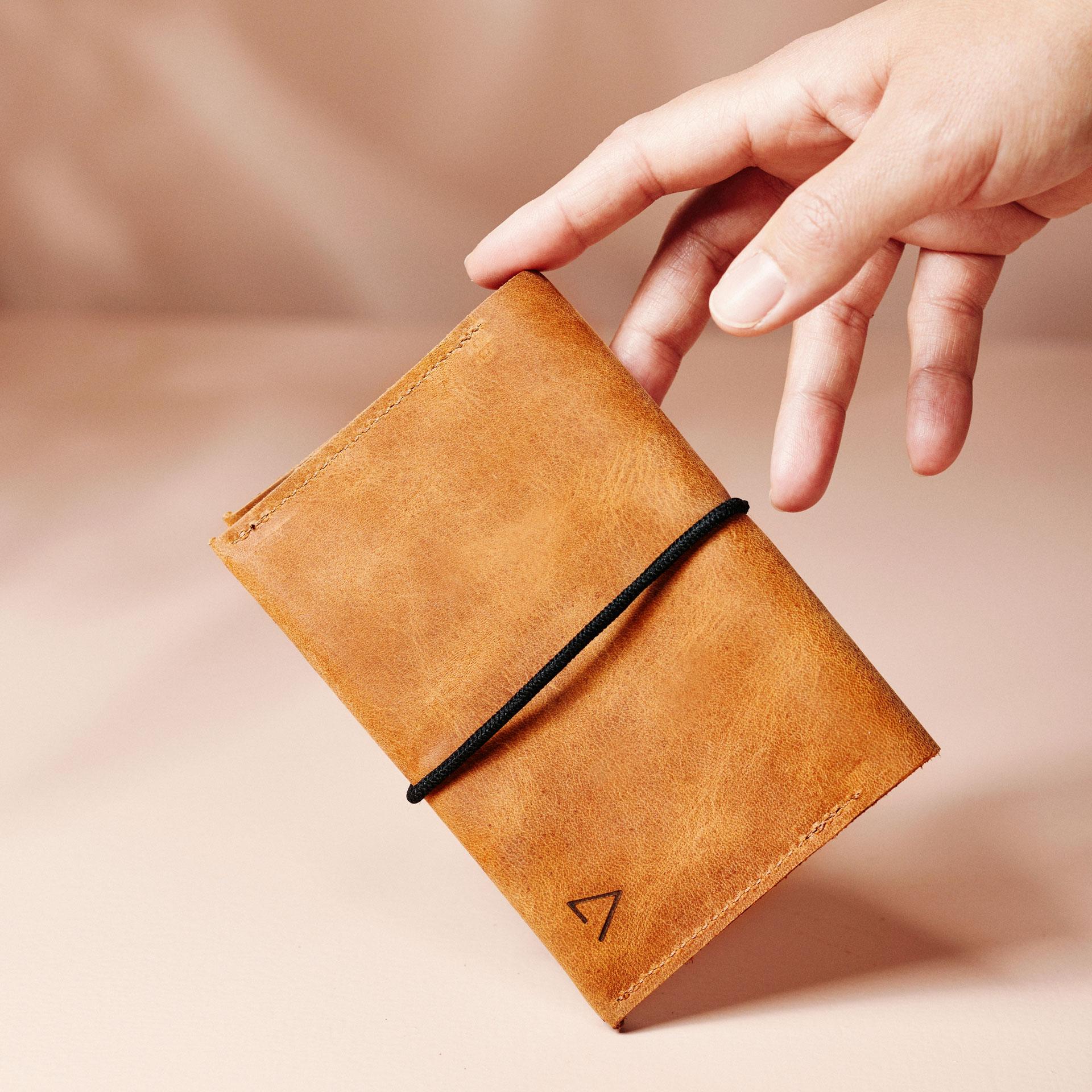 Portemonnaie OLI large im Größenvergleich mit Handy, Laptop und einer Tasse Kaffee.