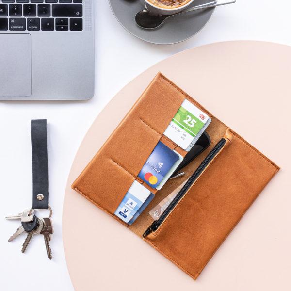 Portemonnaie OLI XLARGE in Cognac geölt aufgeklappt im Größenvergleich mit Laptop, Kaffeetasse und Schlüsselbund