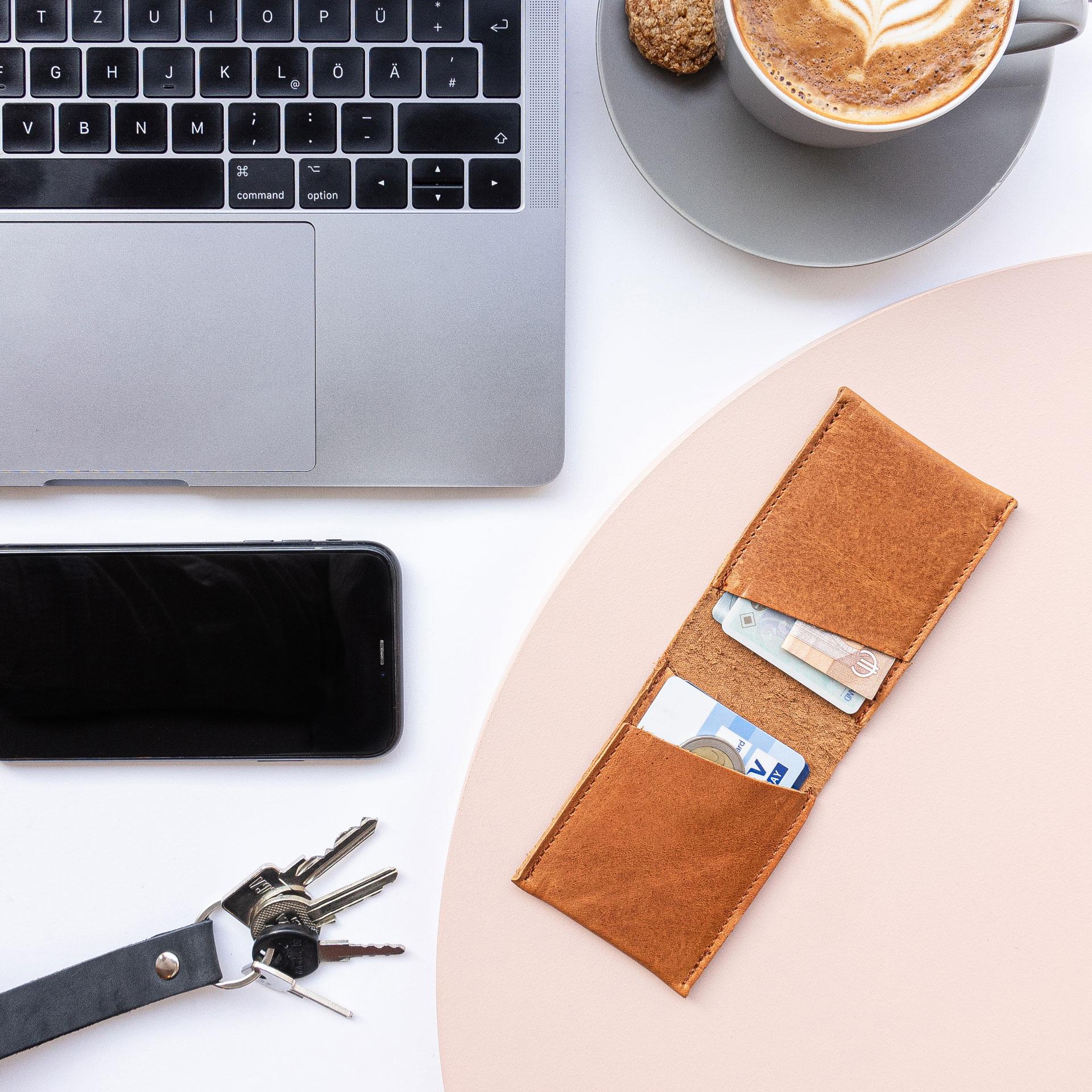 Portemonnaie OLI SMALL geöffnet in Cognac geölt mit Laptop, Kaffeetasse, Handy und Schlüssel