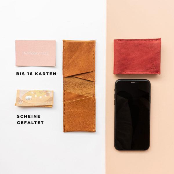 Portemonnaie OLI SMALL in Cognac geölt und Rot im Größenvergleich zu Handy, Visitenkarten und Geldscheinen