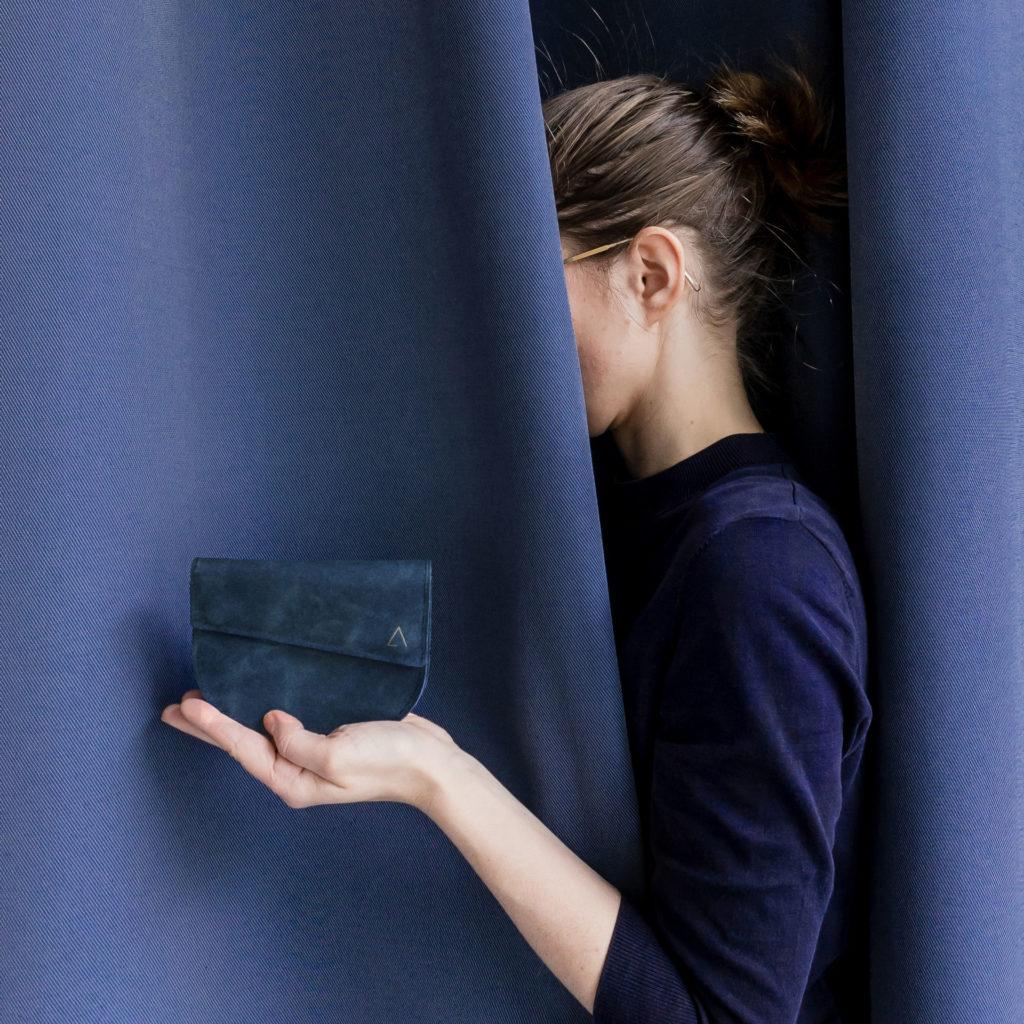 Model hält Portemonnaie UNA dunkelblau aus nachhaltigem Naturleder
