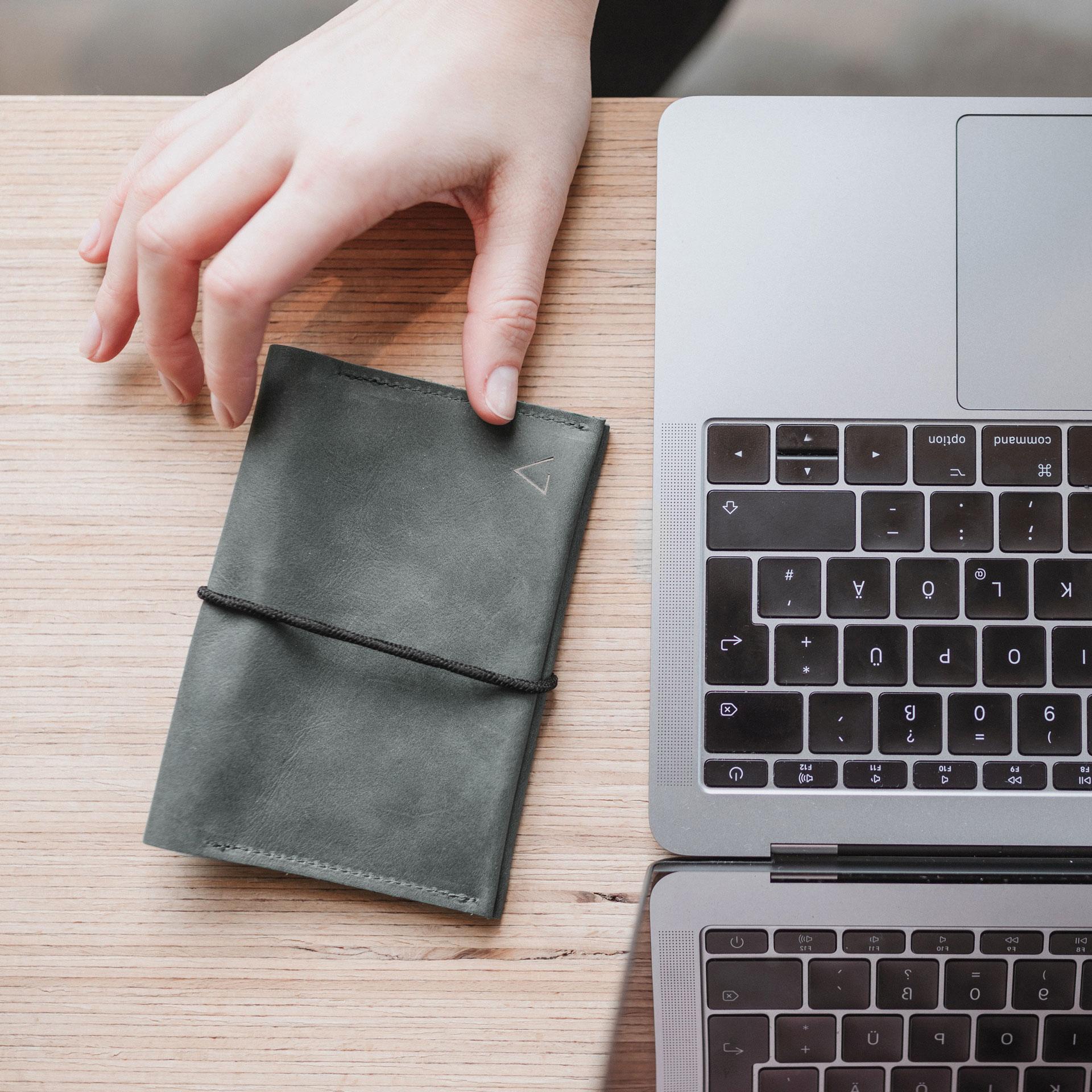 Portemonnaie OLI LARGE in Steingrau mit schwarzem Verschlussband neben Laptop