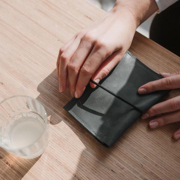 Portemonnaie OLI LARGE in Steingrau mit schwarzem Verschlussband auf Holztisch mit Wasserglas