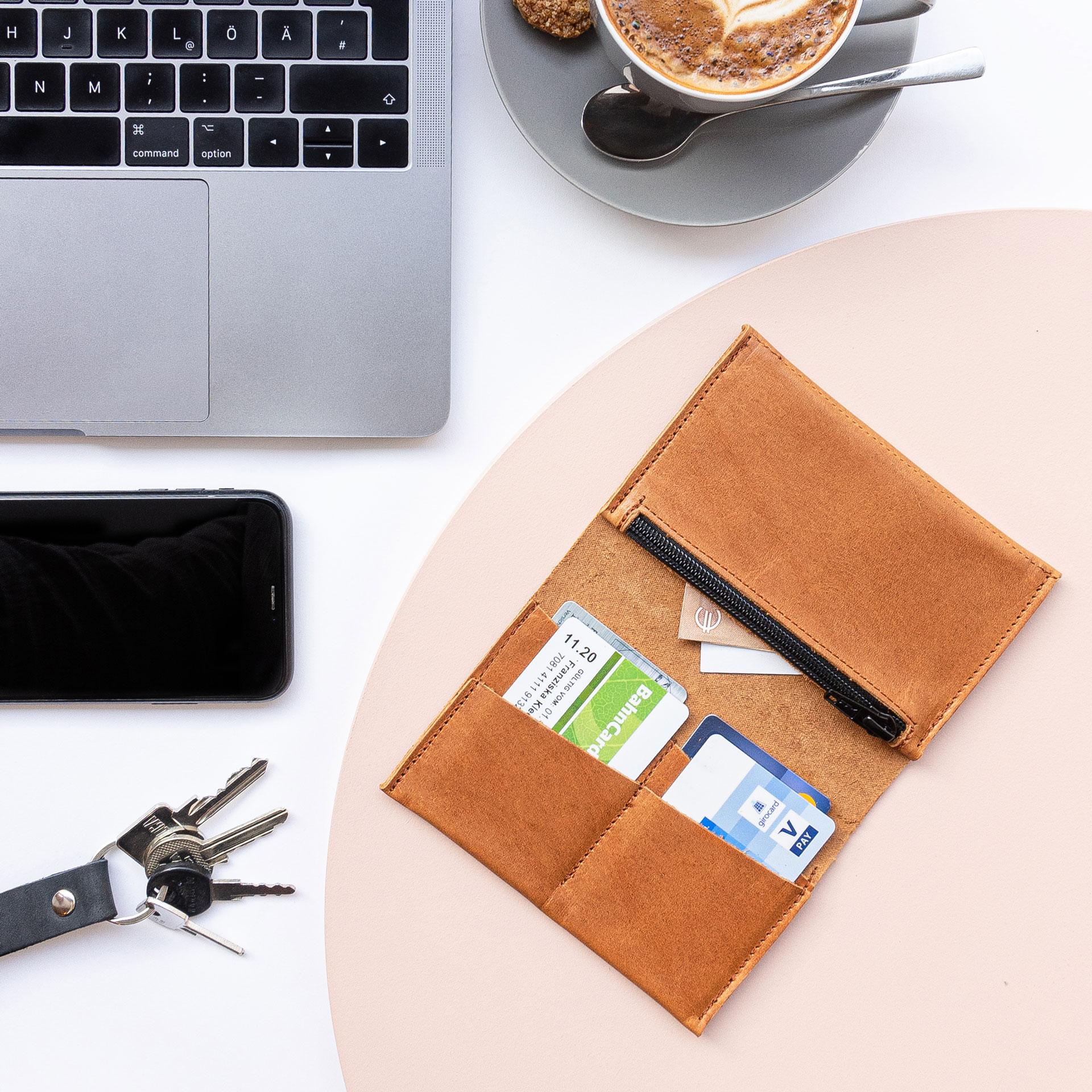 Brieftasche OLI Large von innen mit Karten und Geldscheinen im Größenvergleich mit Laptop, Kaffeetasse, Handy und Schlüsselbund