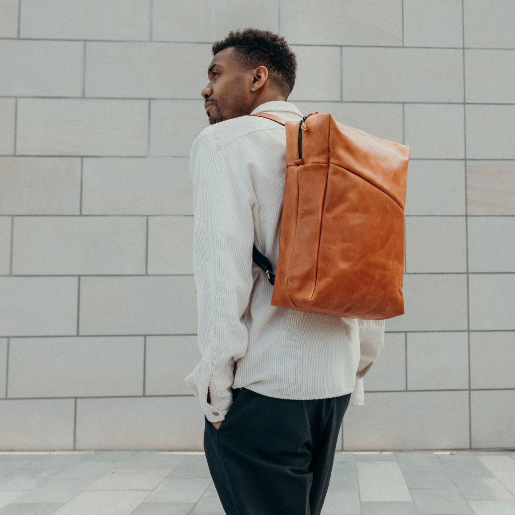 Männliches Model trägt Rucksack NEO Large in der Farbe Cognac geölt auf dem Rücken.