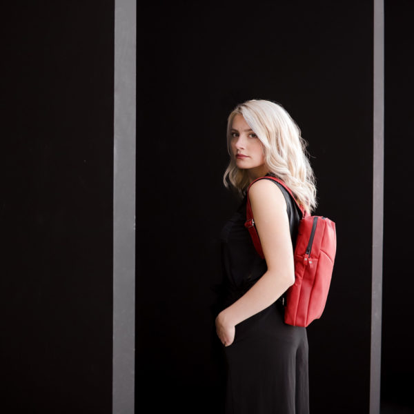 Model trägt Rucksack NEO small in der Farbe Rot.