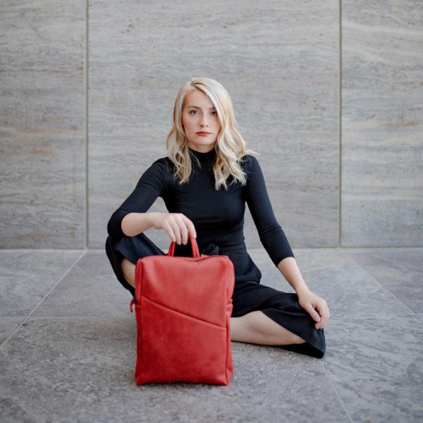 Model sitzt auf dem Boden und hat den Rucksack NEO small in der Farbe Rot vor sich stehen.