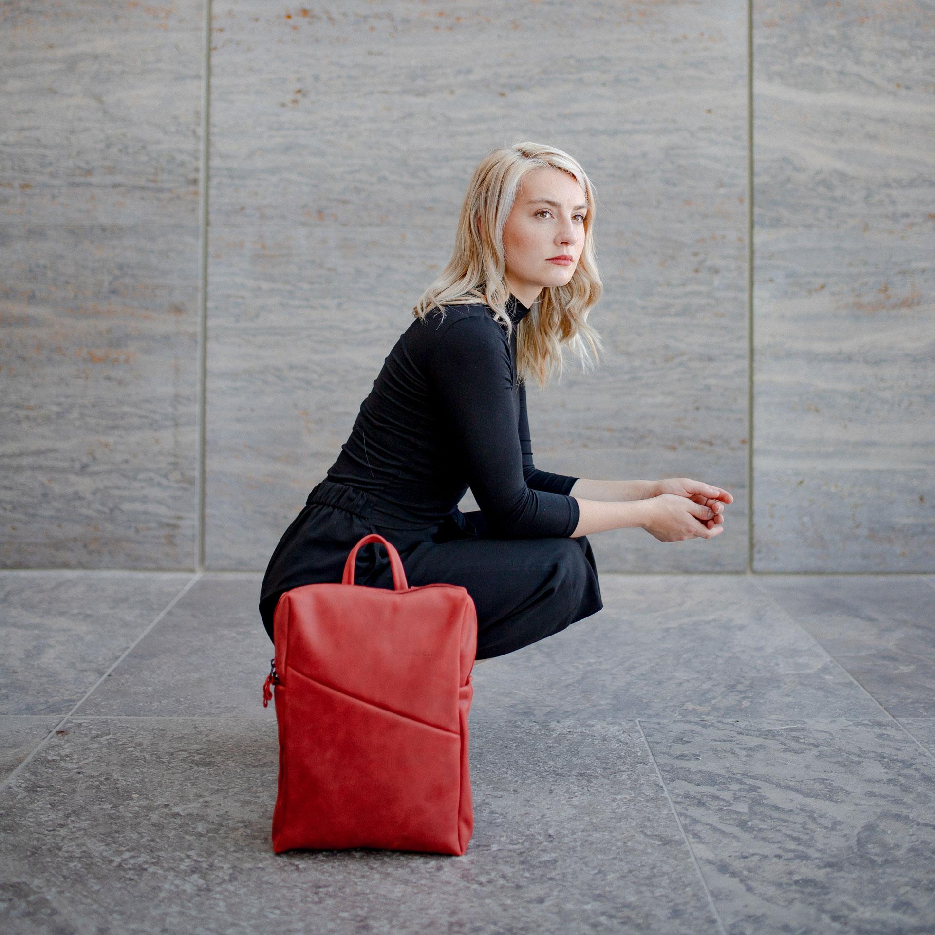 Model hockt auf dem Boden im Seitenprofil und hat den Rucksack Neo small in der Farbe Rot neben sich stehen.