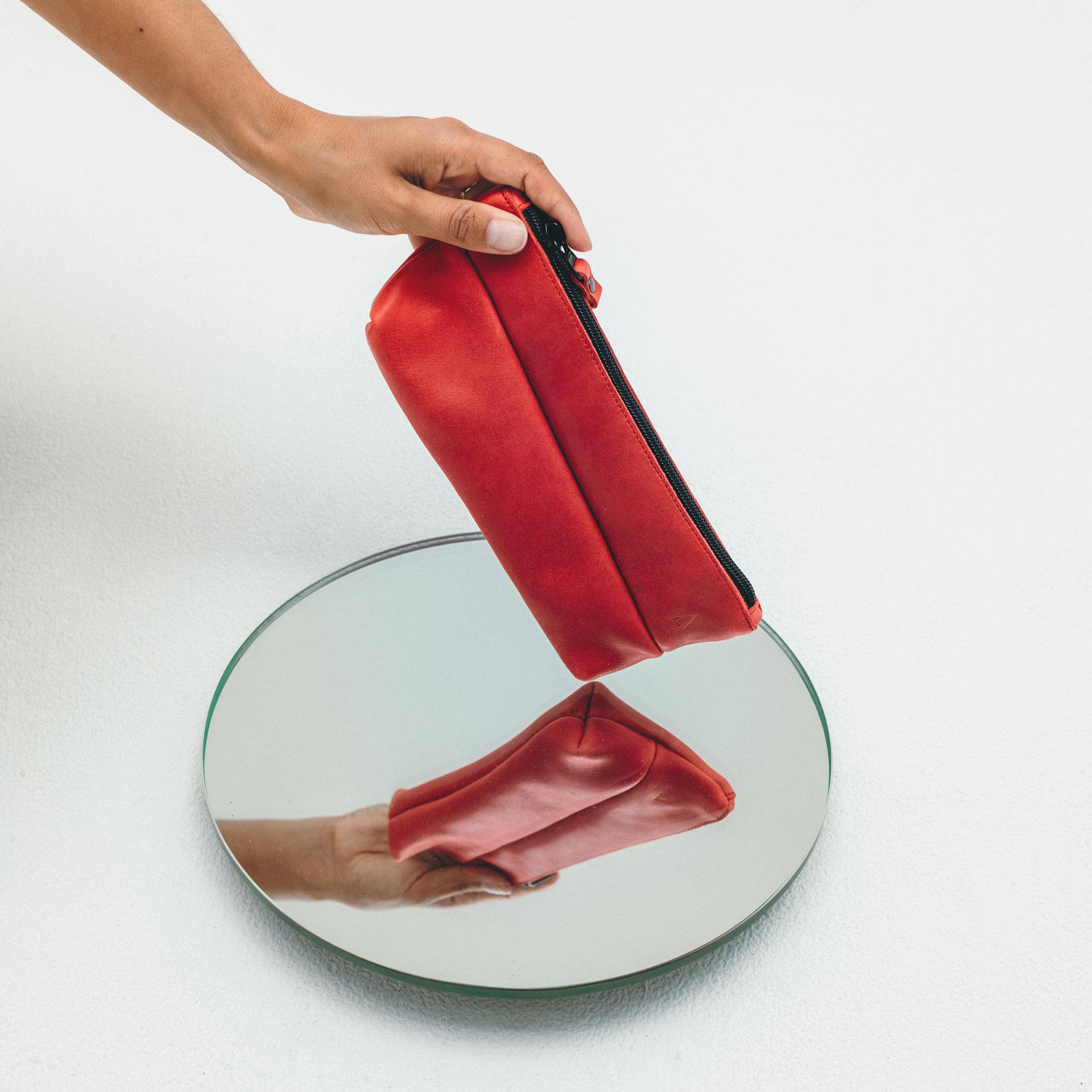 Stifteetui PEN aus nachhaltigem Naturleder in Rot über Spiegel gehalten