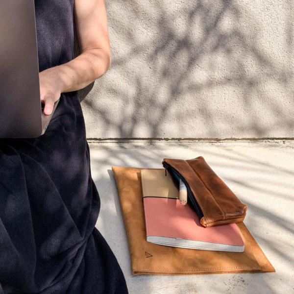 Stifteetui PEN aus nachhaltigem Naturleder in Cognac geölt auf Notizbuch und Laptophülle neben sitzender Frau