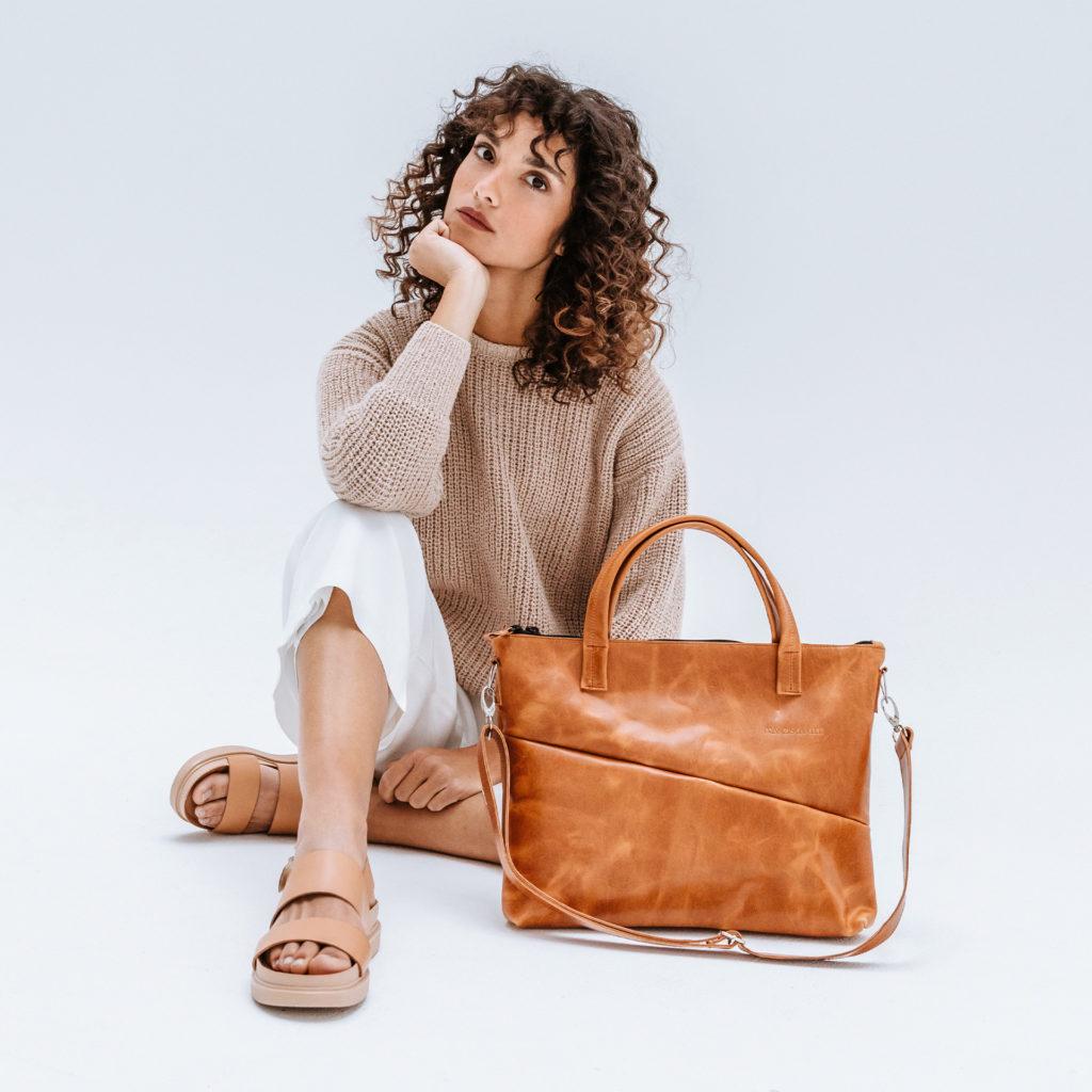 Model sitzend mit nachhaltiger Umhängetasche ANA aus Naturleder