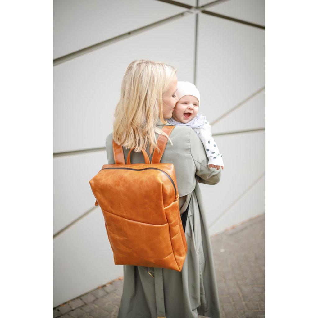 Mutter trägt ihr Kind auf dem Arm und trägt Rucksack NEO Large in Cognac geölt auf dem Rücken.