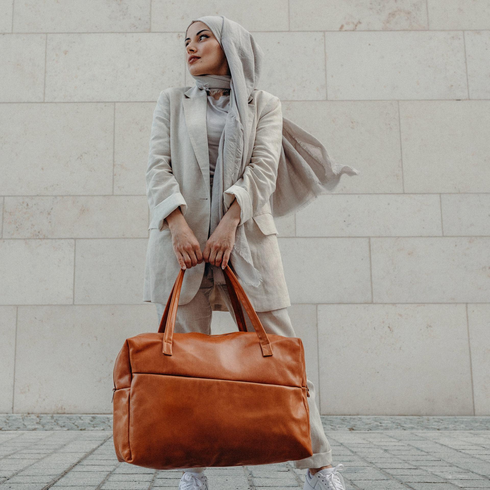 Model mit Weekender Reisetasche RIO mit Henkeln aus cognacfarbenem geölten Naturleder