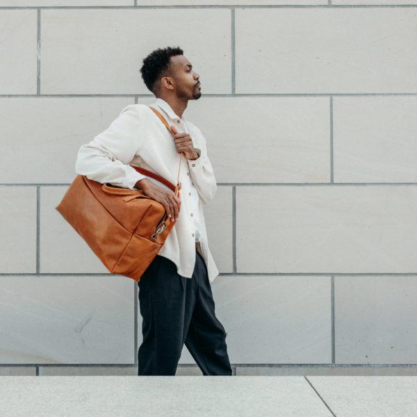 Model mit Weekender Reisetasche RIO mit Henkeln und Schultertasche aus cognacfarbenem geölten Naturleder