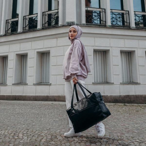 Model mit Weekender Reisetasche RIO mit Henkeln aus schwarzem geölten Naturleder