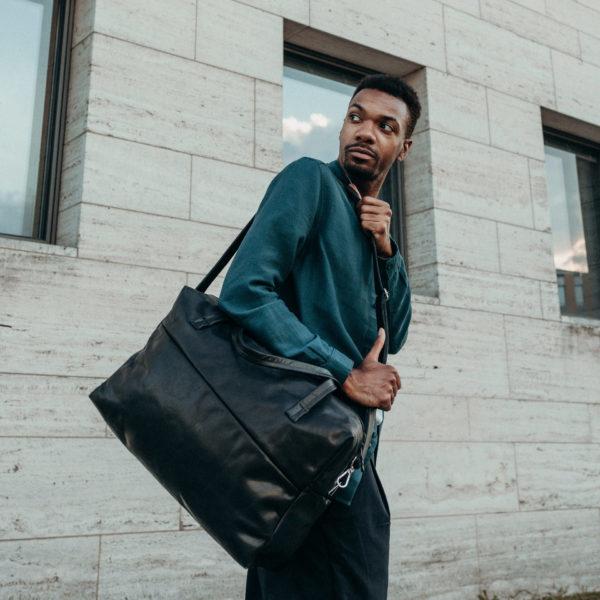 Model mit Weekender Reisetasche RIO mit Henkeln und Schultergurt aus schwarzem geölten Naturleder
