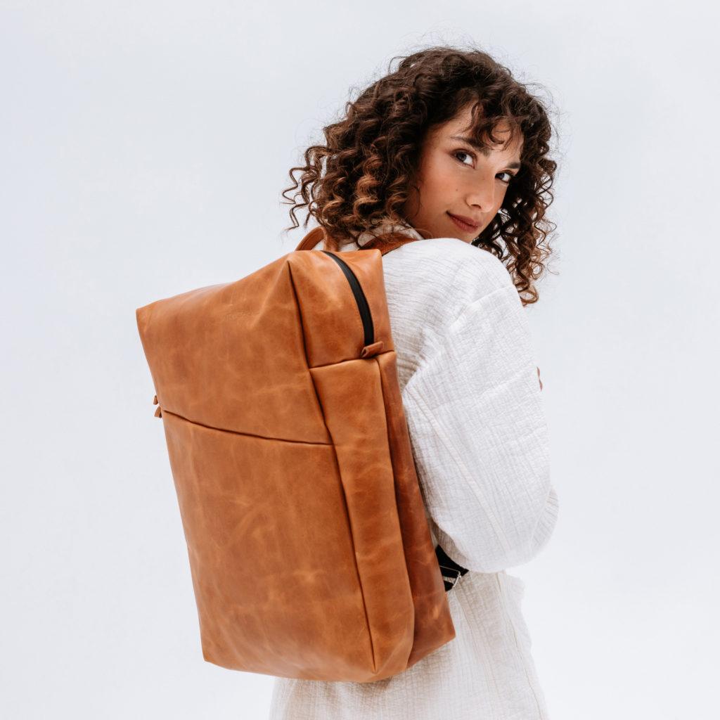 Model mit Rucksack Neo Large aus cognac geöltem Naturleder