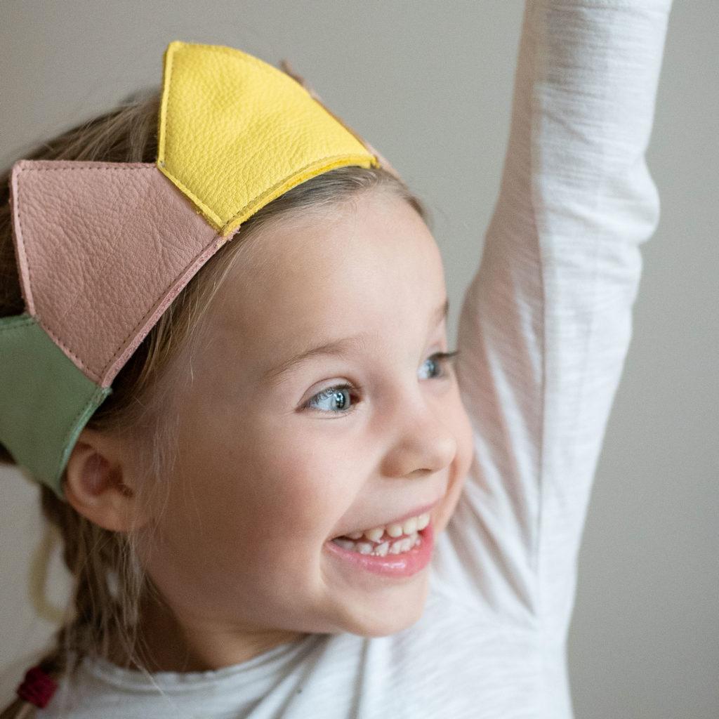 Mädchen trägt konfigurierte Geburtstagskrone in Gelb, Rosa und Mint