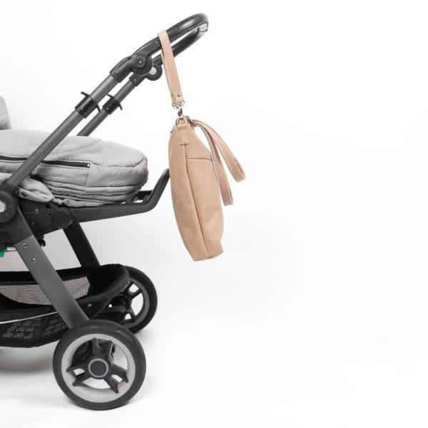 Seitenansicht der Wickeltasche MIA MIDI aus nachhaltigem Naturleder in Hellbraun mit Aufhängungen an Kinderwagen befestigt