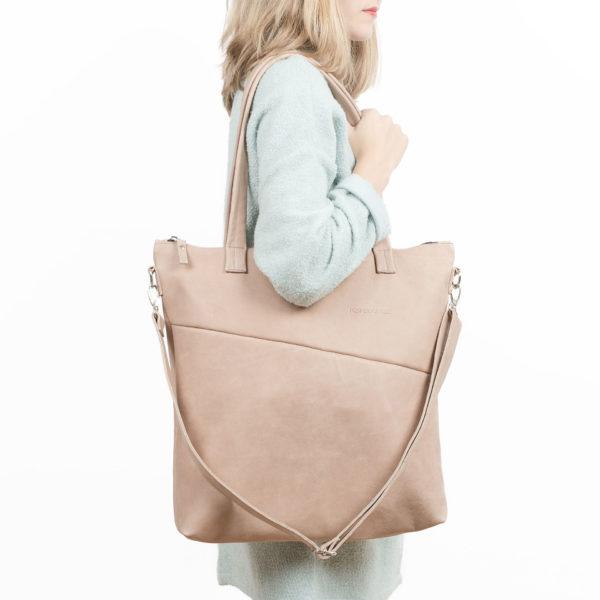 Model trägt Wickeltasche MIA MIDI aus Naturleder in Hellbraun mit langen Henkeln und abnehmbarem Umhängegurt