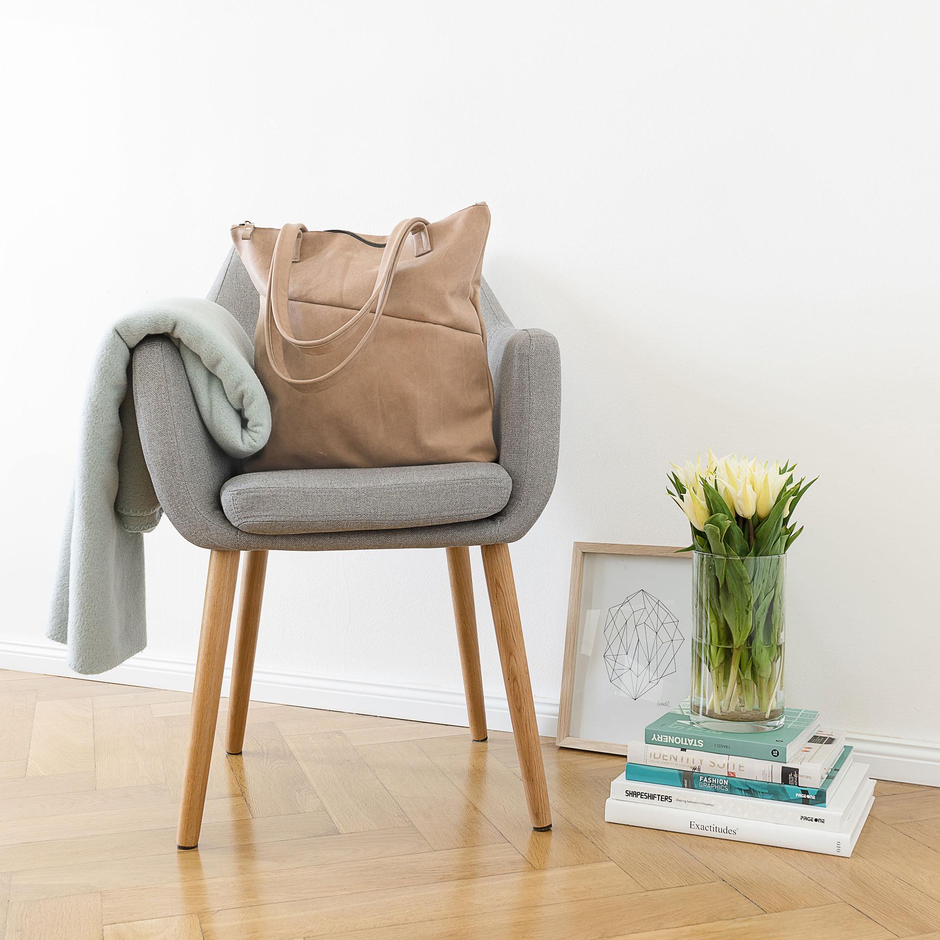 Moodshot Wickeltasche MIA MIDI aus nachhaltigem Naturleder in Steingrau auf einem Stuhl stehend
