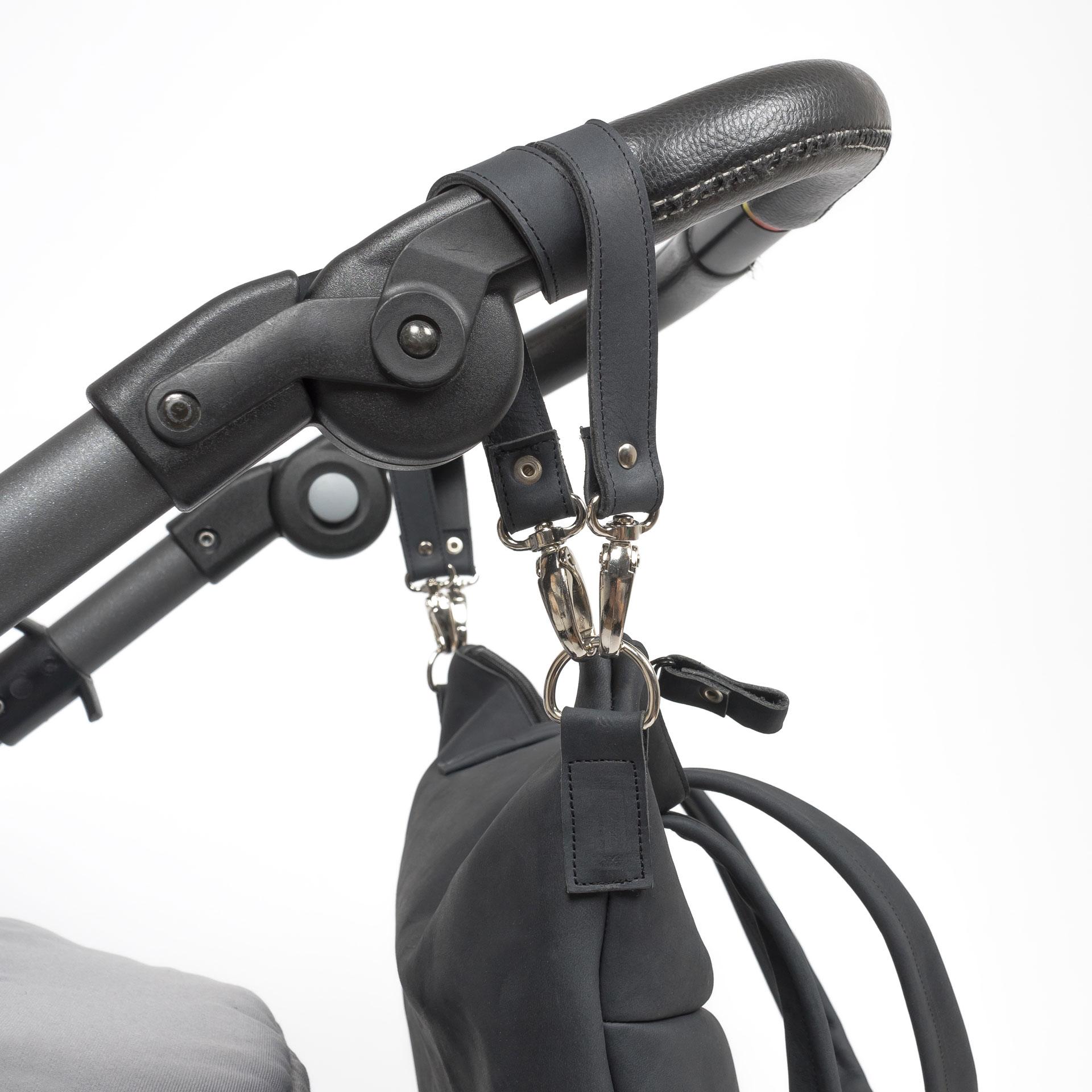 Detailaufnahme der Kinderwagenaufhängung für Wickeltasche MIA MIDI aus nachhaltigem Naturleder in Kohle