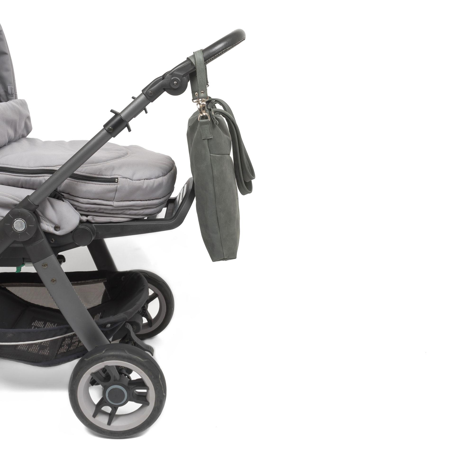 Seitenansicht der Wickeltasche MIA MIDI aus nachhaltigem Naturleder in Steingrau mit Aufhängungen an Kinderwagen befestigt