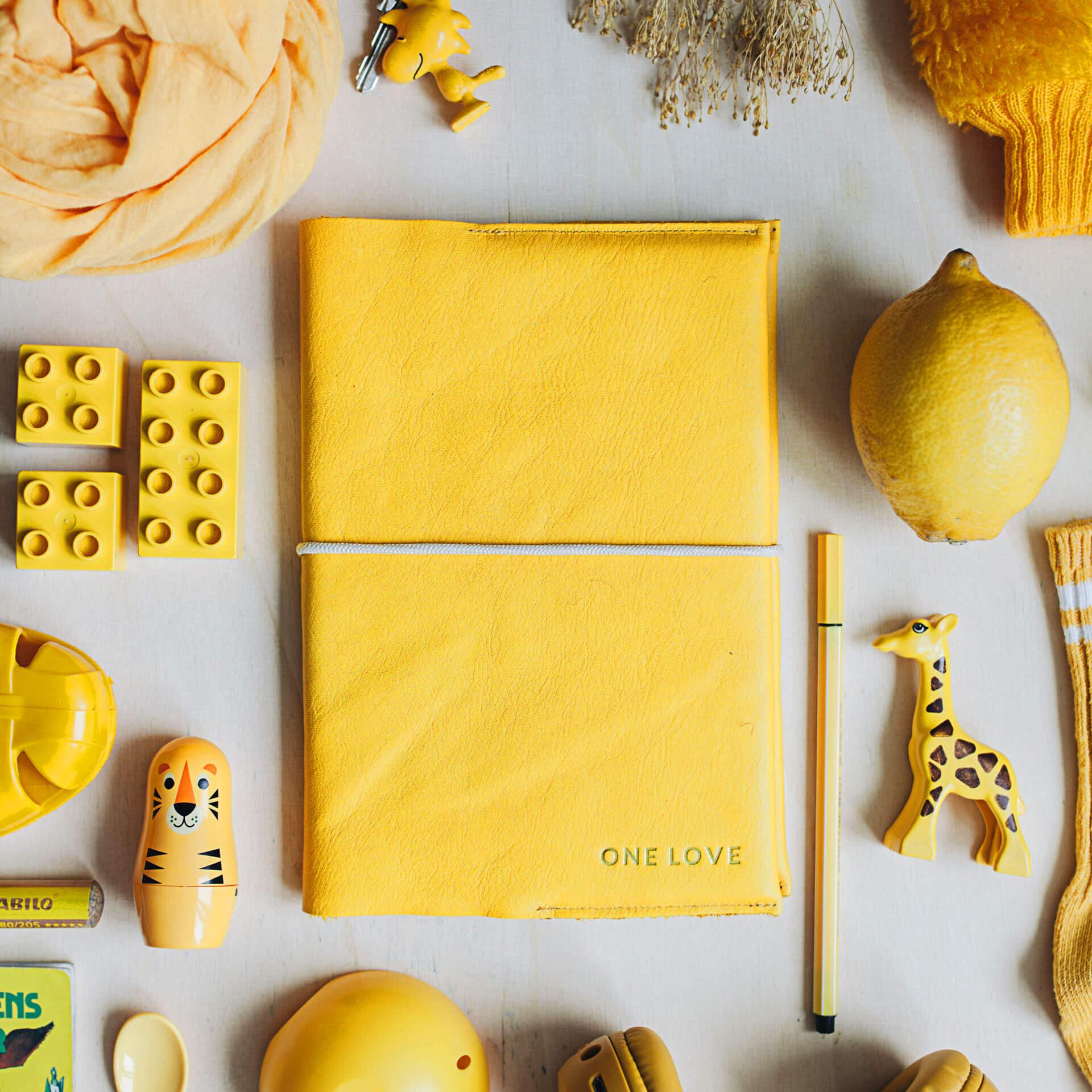 Mood Shot U-Hefthülle EVE aus nachhaltigem Naturleder in Curry mit individueller Prägung in Gold und cremefarbenem Verschlussband neben gelbem Spielzeug