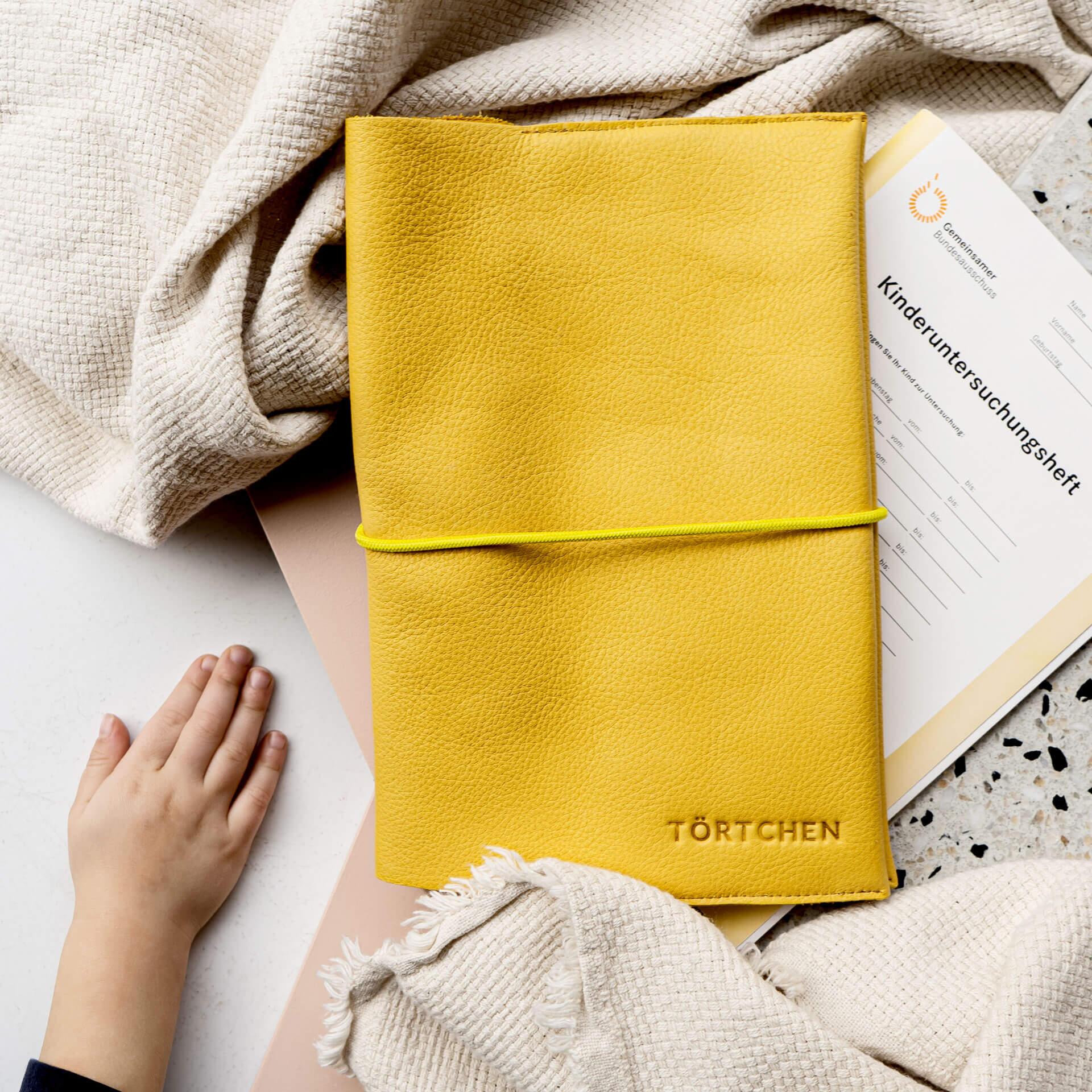Auf unseren U-Hefthüllen kannst du einen Wunschtext deiner Wahl verewigen lassen. In diesem Fall: Törtchen.
